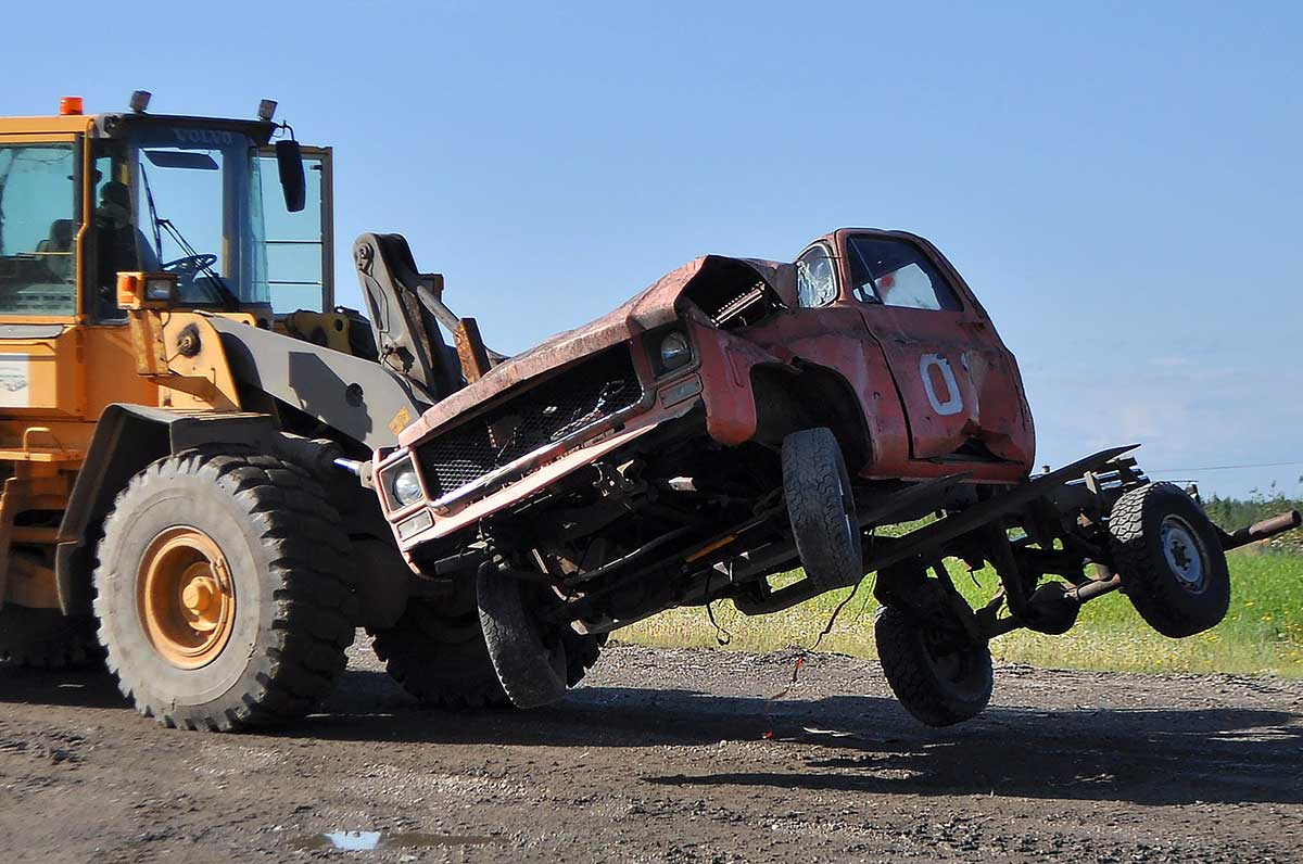 A contractor uses a forklift to pick up a junked truck