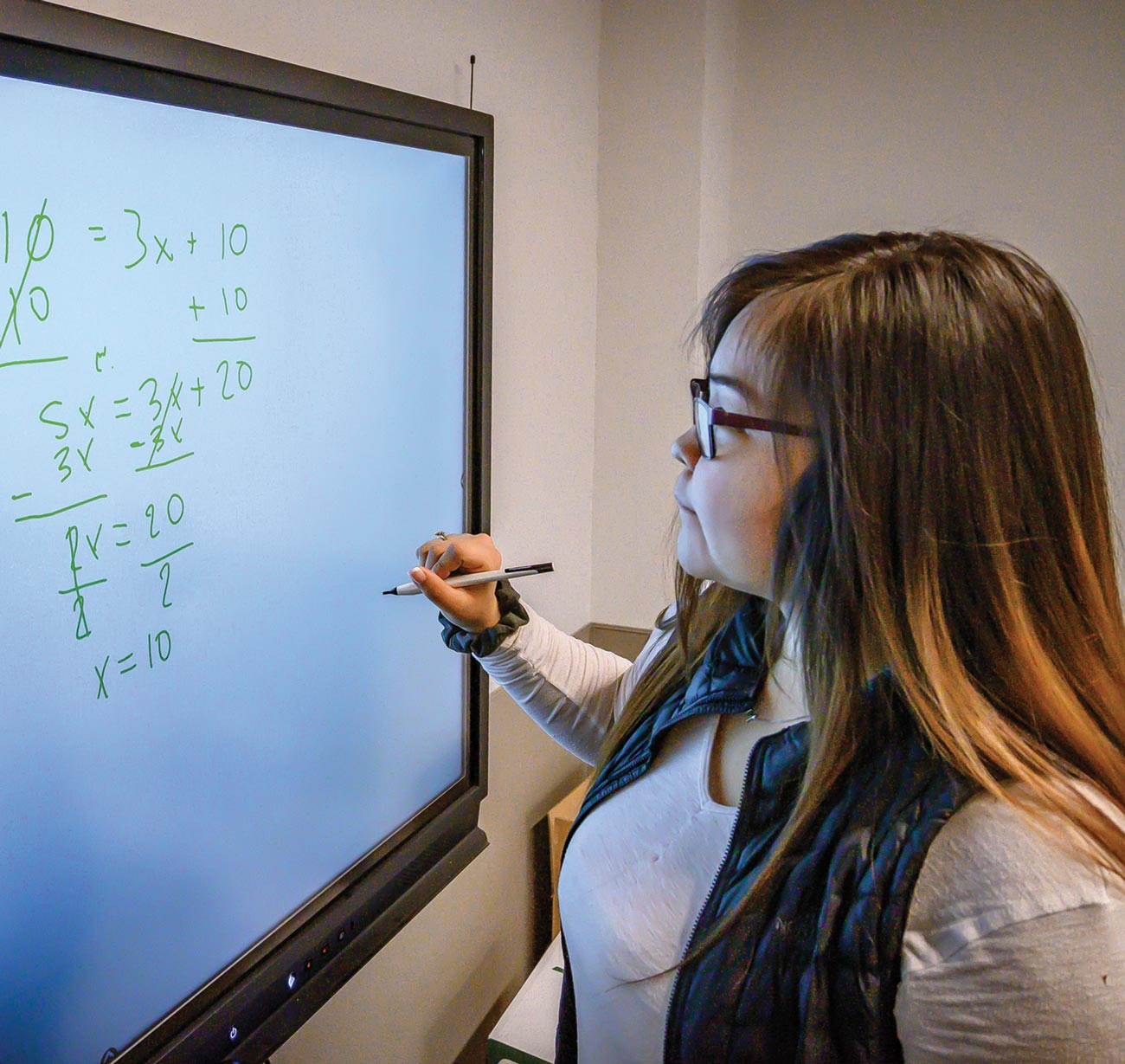 A student at the Kusilvak Career Academy uses technology in the form of an electronic whiteboard to facilitate learning